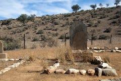 Tombe avec la pierre tombale superficielle par les agents, paysage aride à l'arrière-plan image libre de droits