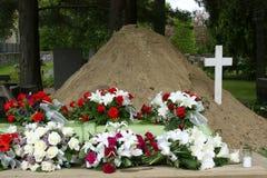 Tombe avec les fleurs et la croix photos stock
