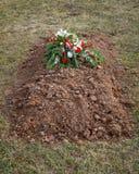 Tombe fraîchement creusée avec des fleurs de cimetière sur la terre photos stock