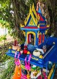 Tombeau extérieur thaïlandais traditionnel coloré de maison d'esprit avec des guirlandes de fleur sous la nuance d'arbre photo stock