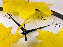 Tombent de retour, l'horaire d'hiver Feuilles d'horloge et de jaune Image libre de droits