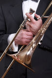 Tombone on Tux. A slide trombone is held in front of an orcestra musician's tuxedo Royalty Free Stock Image