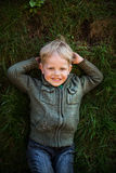 Tomboy lying on grass and smiling. Portrait of a laughing little boy lying on green grass Stock Photo