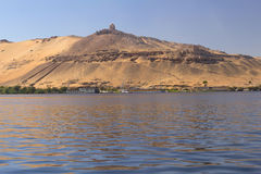 Tombs of the Nobles (Aswan, Egypt ). Tombs of the Nobles. Nile boats are anchored at the shore. (Aswan, Egypt Royalty Free Stock Image
