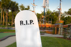Tombstone. Rest in peace tombstone with pirate ship in the background at sunset Stock Images