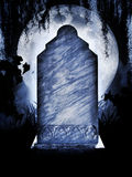Headstone and moon. Concept for Halloween with a marble tombstone or grave stone and a large moon glowing in the background Stock Photo