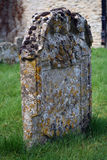 A tombstone in an ancient graveyard. A moss and lichen covered tombstone in an ancient English churchyard Royalty Free Stock Photos