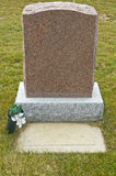 Tombstone in a Cemetery. A pink granite tombstone in a graveyard Royalty Free Stock Image