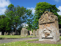 Tombstone in Church Graveyard. A tombstone in a sunny churchyard cemetery surrounded by trees Stock Image