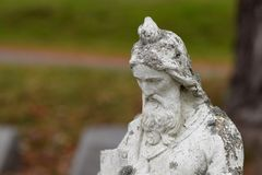 Tombstone Closeup with Moss and Grime. Ancient tombstone crusted with moss and grime. Closeup image with graveyard blurred in the bokeh Stock Images