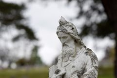 Tombstone Closeup with Moss and Grime. Ancient tombstone crusted with moss and grime. Closeup image with graveyard blurred in the bokeh Stock Photos
