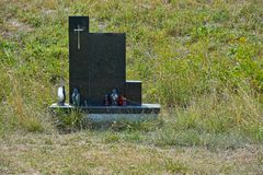 Tombstone with a cross. In the middle of green grass Royalty Free Stock Photography
