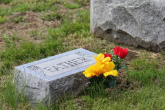 Tombstone with Father and flowers. Tombstone with the word Father and artificial flowers in a cemetery Royalty Free Stock Photo