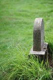 Tombstone in grass. Simple tombstone in grass  in grass with copy space Stock Photography