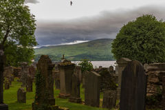Tombstones in cemetery with flying bird and lake in background Stock Photo