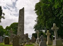 Tombstones in a cemetery with round tower royalty free stock images