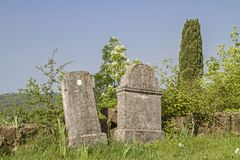 Tombstones in the wilderness of Istria. Old gravestones in the abandoned graveyard of a deserted and dilapidated village in Istria stock image