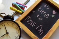 Tome à frase da primeira etapa escrito à mão colorido no quadro, no despertador com motivação e nos conceitos da educação Ele tem fotografia de stock