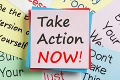 Tome a ação escrita agora na nota Imagem de Stock Royalty Free