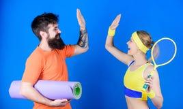 Tome cinco Treinamento desportivo dos pares com esteira da aptidão e raquete de tênis Músculos e corpo fortes Equipamento de espo imagem de stock
