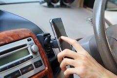 Tome el teléfono del montaje en la rejilla de ventilación del aire del tenedor Imagen de archivo libre de regalías