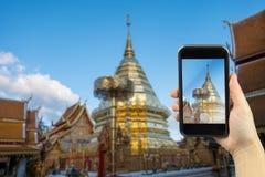 tome la foto por smartphone Wat Phra That Doi Suthep es turístico en Fotografía de archivo