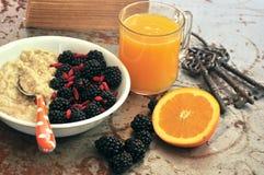 Tome o café da manhã com amoras-pretas, sementes do goji e suco de laranja imagens de stock royalty free