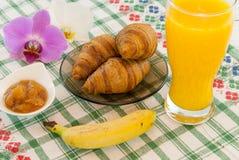 Tome o café da manhã com as bananas dos croissant do suco de laranja com orquídea que as flores de lado recorrem conceito do amor foto de stock