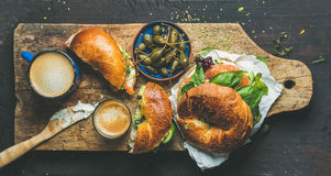 Tome o café da manhã com bagel, café do café e alcaparras na bacia azul Imagem de Stock Royalty Free