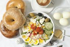 Tome o café da manhã com café, bagels, salada e ovos Fotografia de Stock Royalty Free