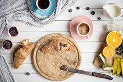 Tome o café da manhã com café, croissant, queques e frutos na tabela de madeira branca Fotos de Stock Royalty Free