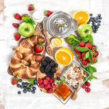 Tome o café da manhã com croissant, muesli, bagas frescas, frutos saúde Fotografia de Stock