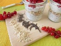 Tome o café da manhã com iogurte, sementes do chia, farinha de aveia e bagas Imagem de Stock