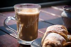 Tome o café da manhã com o copo do café preto, croissant na tabela de madeira Imagem de Stock Royalty Free