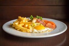 Tome o café da manhã com os ovos e o tomate fritados do bacon da batata Imagens de Stock