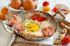 Tome o café da manhã com ovos fritos e bacon - almoço completo Imagem de Stock