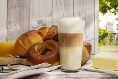 Tome o café da manhã com pão, bolos, macchiato do Latte e suco de laranja Imagem de Stock