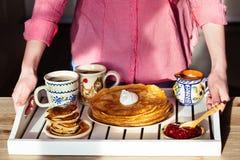 Tome o café da manhã com panquecas, creme de leite, doce e bebidas quentes em uma bandeja foto de stock royalty free