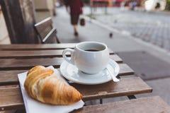 Tome o café da manhã com café preto e croissant na tabela de madeira em um café exterior Cidade em um fundo imagem de stock