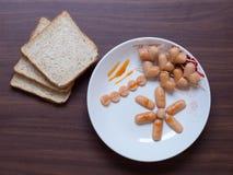 Tome o café da manhã com a salsicha do pão e do coração na tabela Imagem de Stock Royalty Free