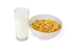 Tome o café da manhã com vidro do leite e dos flocos em uma bacia Imagem de Stock Royalty Free