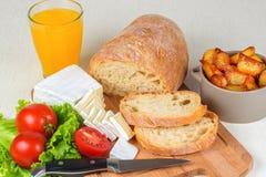 Tome o café da manhã do pão, queijo, tomates, batatas e por todo o lado na salada em um close up Foto de Stock Royalty Free