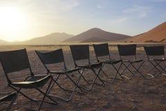 Tome o café da manhã em cadeiras em um círculo no deserto Fotos de Stock