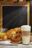 Tome o café da manhã no café, pão, bolos, ovo, macchiato do Latte, suco de laranja Fotografia de Stock Royalty Free