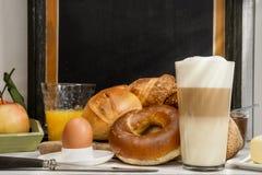 Tome o café da manhã no café, pão, bolos, ovo, macchiato do Latte, suco de laranja Imagens de Stock
