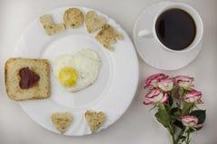 Tome o café da manhã para amantes, ovos mexidos, café, rosas dão forma foto de stock royalty free