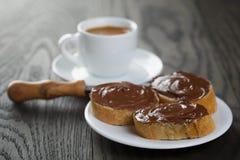 Tome o café da manhã com fatias do café e do baguette com propagação do chocolate Fotografia de Stock Royalty Free