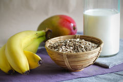 Tome o pequeno almoço com farinha de aveia, as bananas, a manga e leite rolados Foto de Stock Royalty Free