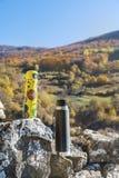 Tome parte num piquenique na montanha alta do outono com dois thermoses Imagem de Stock Royalty Free