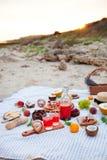 Tome parte num piquenique na praia no por do sol na manta, no alimento e na bebida brancos fotos de stock